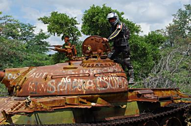 Abandoned tanks and other military equipment are left to waste away on the side of the road in Angola.